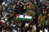 Palestinians crowd around the coffin of late Palestinian leader Yasser Arafat inside the Muqataa Arafat's destroyed office compound as it arrived...