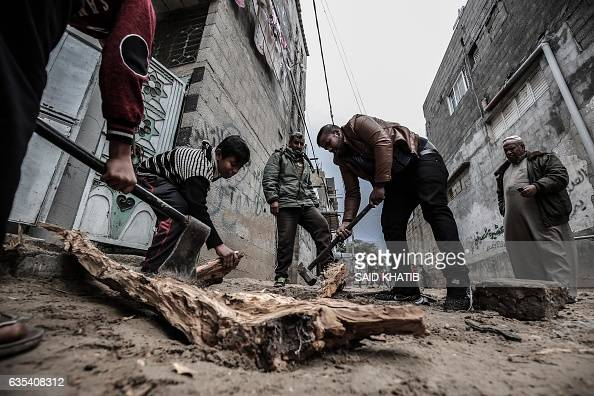 TOPSHOT Palestinians cut wood following heavy rainfall during a cold front in Rafah in the southern Gaza Strip on February 15 2017 / AFP / SAID KHATIB