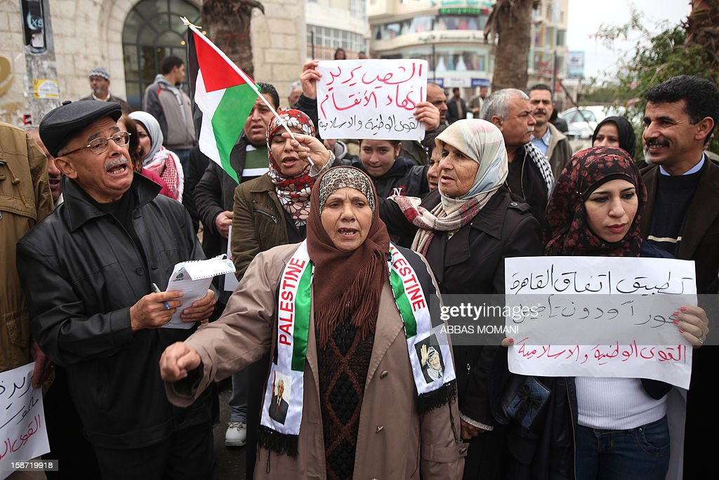 Palestinians demonstrate in the West Bank city of Ramallah calling for an end in the political division and commitment to the reconciliation agreement between rival Palestinian factions Hamas and Fatah on December 26, 2012. AFP PHOTO / ABBAS MOMANI