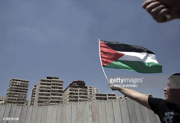Palestinians demonstrate near Israel's separation barrier enclosing the Palestinian refugee camp of Shuafat in east Jerusalem on June 12 against the...