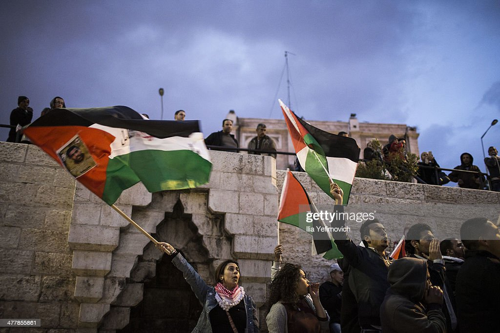 Palestinians demonstrate outside the Damascus gate of the old city of Jerusalem on March 11 2014 in Jerusalem Israel Following the two funeral of...