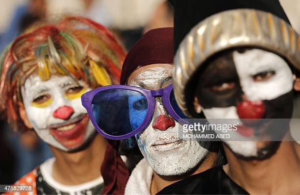 Palestinians dressed as clowns pose for a picture during an event for children organised by the Pink Panther group to mark the day of the Palestinian...