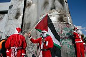 Palestinians dressed up as Santa Claus demonstrate in front of the Israeli controversial separation wall in the West Bank city of Bethlehem on...