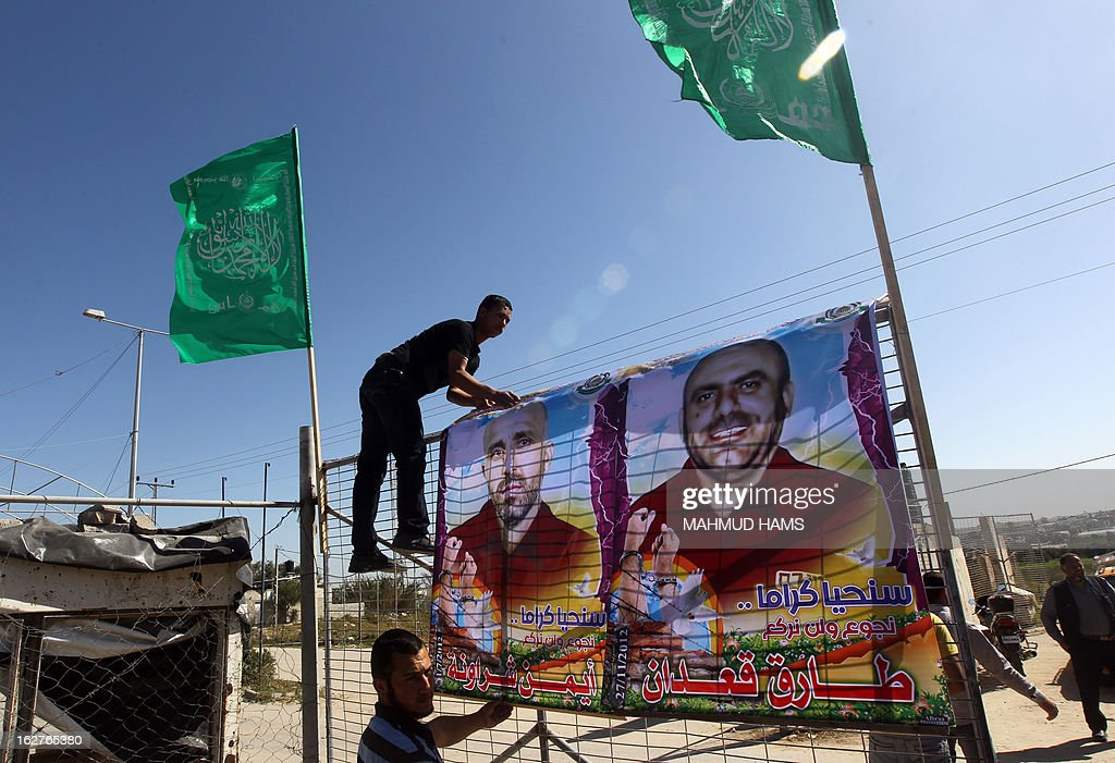Palestinians erect posters of hunger-striking Palestinian prisoners during a protest following the death of Arafat Jaradat, who died in an Israeli prison, at Erez border crossing between Israel and the northern Gaza Strip on February 26, 2013. Gaza militants from Fatah's Al-Aqsa Martyrs Brigades fired a rocket at Israel as a 'preliminary response' after one of its members died in an Israeli jail.