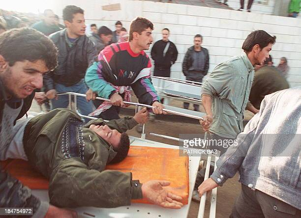 Palestinians evacuate a man on February 25 wounded during the Cave of the Patriarchs massacre carried out by Jewish settler Baruch Goldstein who...