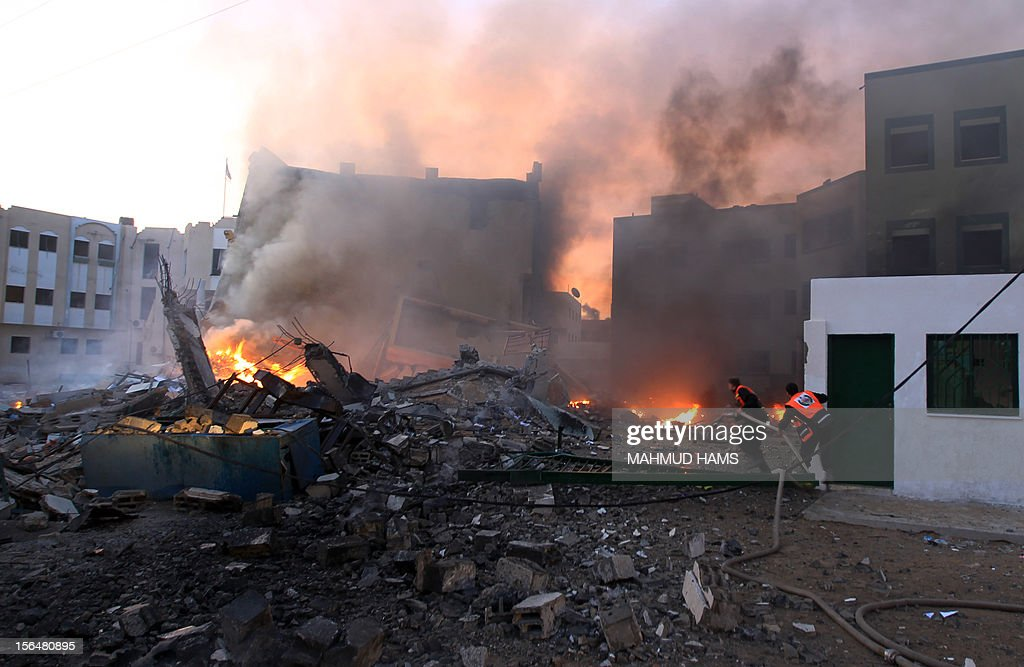 Palestinians extinguish fire after Israeli air strikes targeted the interior ninistry building in Gaza City, on November 16, 2012 . AFP PHOTO/MAHMUD HAMS