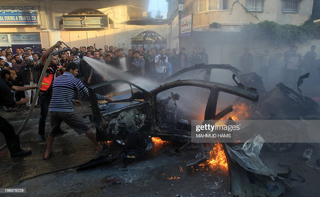 Palestinians extinguish fire from the car of Ahmed Jaabari, head of the military wing of the Hamas movement, the Ezzedin Qassam Brigades, after it was hit by an Israeli air strike in Gaza City on November 14, 2012. The top Hamas commander Ahmed al-Jaabari was killed in an Israeli air strike , medics and a Hamas source told . AFP. AFP PHOTO/MAHMUD HAMS