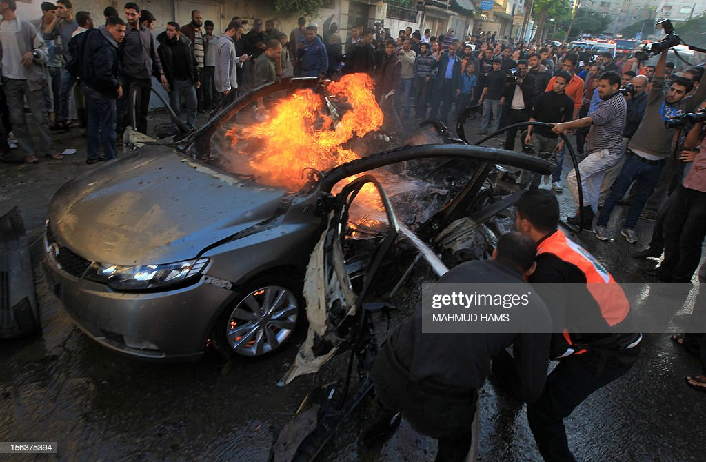 Palestinians extinguish fire from the car of Ahmed Jaabari, head of the military wing of the Hamas movement, the Ezzedin Qassam Brigades, after it was hit by an Israeli air strike in Gaza City on November 14, 2012. The top Hamas commander Ahmed al-Jaabari was killed in an Israeli air strike , medics and a Hamas source told . AFP PHOTO/MAHMUD HAMS