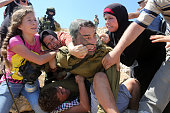 Palestinians fight to free a Palestinian boy held by an Israeli soldier during clashes between Israeli security forces and Palestinian protesters...