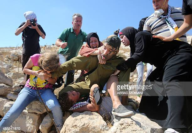 Palestinians figth to free a Palestinian boy held by an Israeli soldier during clashes between Israeli security forces and Palestinian protesters...