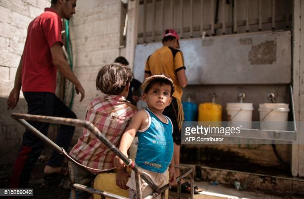 TOPSHOT Palestinians fill bottles and buckets with water at a communal water tank at alShati refugee camp in Gaza City on July 16 as the power supply...