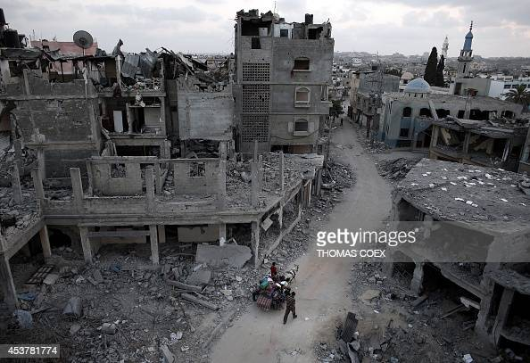 Palestinians flee their destroyed neighbourhood on a horse and cart in the northern Gaza Strip city of Beit Hanun on August 18 2014 Prime Minister...
