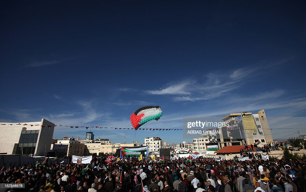 Palestinians fly balloons bearing the colours of their national flag as Palestinian president Mahmud Abbas (unseen) delivers a speech upon his arrival in the West Bank city of Ramallah on December 2, 2012, after winning upgraded United Nations status for the Palestinians earlier in the week. Abbas said 'Palestine has accomplished a historic achievement at the UN,' three days after the United Nations General Assembly granted the Palestinians non-member state observer status in a 138-9 vote. AFP PHOTO / ABBAS MOMANI
