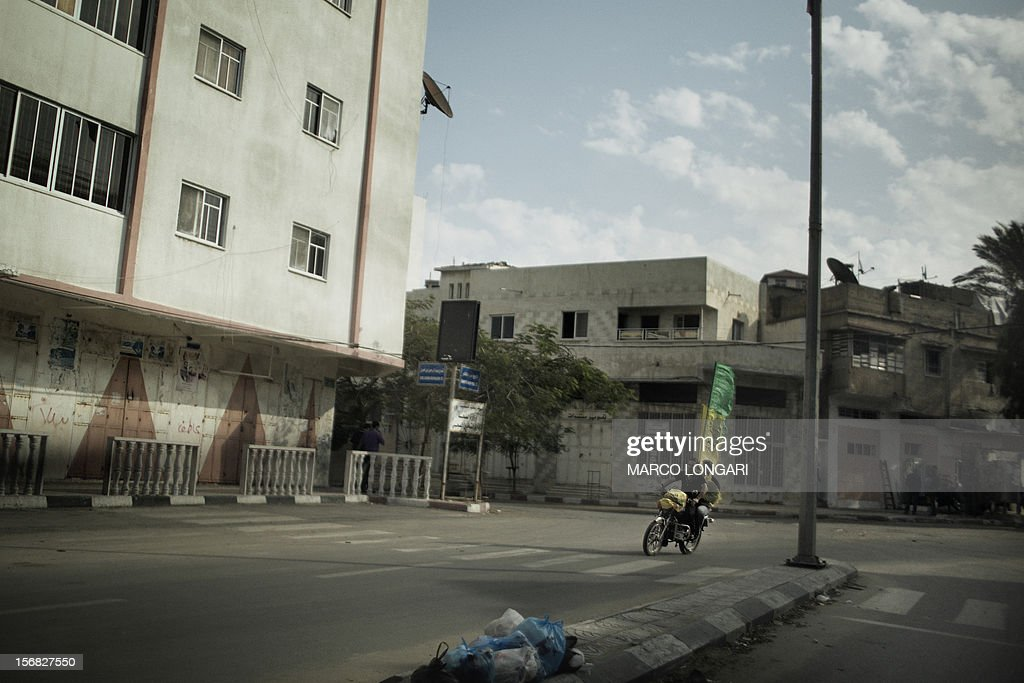 Palestinians fly Fatah and Hamas flags from the back of a motorbike as they celebrate the ceasefire in Gaza City on November 22, 2012. Israeli politicians returned to the campaign trail as the streets of Gaza came back to life after a truce ended eight days of bloodshed, with both sides claiming victory while remaining wary.