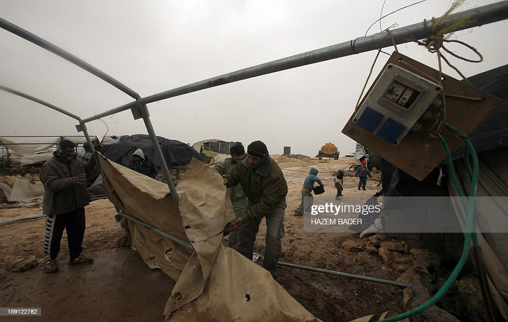 Palestinians from al-Nawajaa family repair their tent damaged during storms that are engulfing the Levant region on January 8, 2013, in the hills south Yatta close to the West Bank town of Hebron. AFP PHOTO / HAZEM BADER