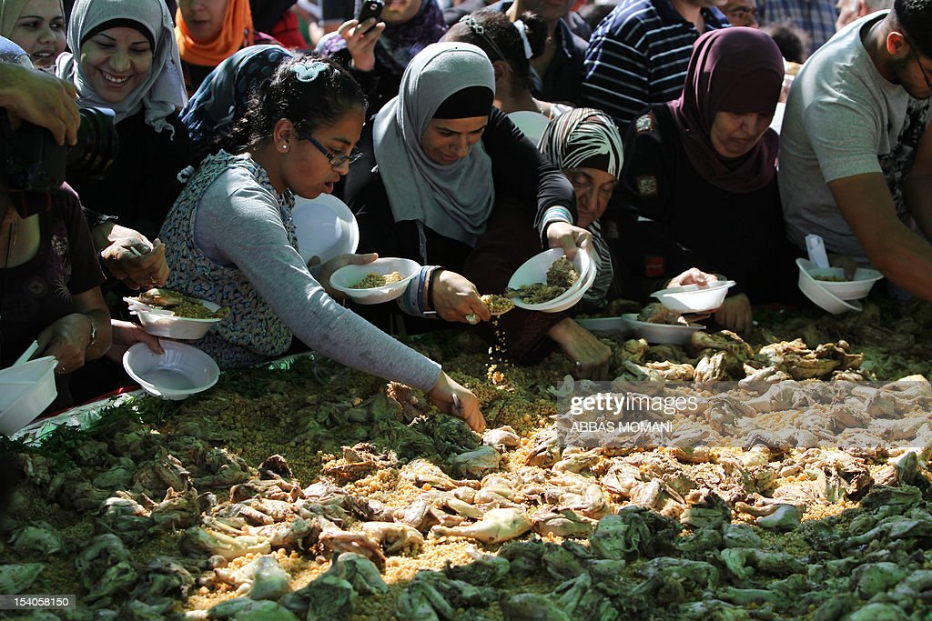 Palestinians from Ramallah serve themselves from what they call the biggest Maftul dish in the world during an event in the West Bank city on October 13, 2012. Maftul is a typical Palestinian home-made pasta recipe with chickpees, cracked wheat and chicken which was prepared in a 5x5 meter especially-made serving plate, using 100 kgs of each ingredient and 500 chicken. AFP PHOTO/ABBAS MOMANI