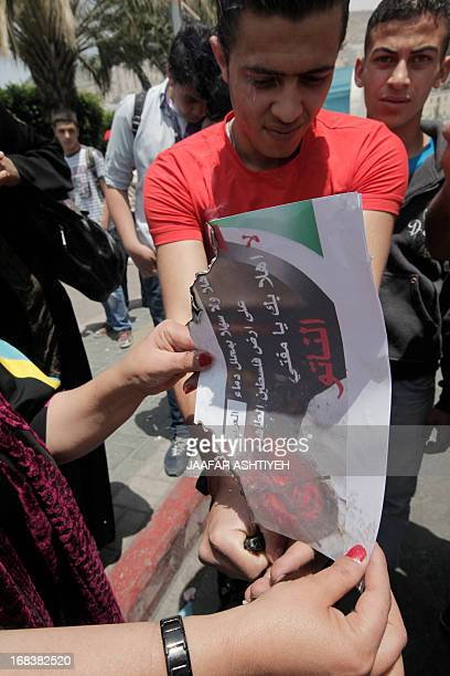 Palestinians from the Popular Front for the Liberation of Palestine burn a poster featuring chairman of the International Union of Muslim Scholars...