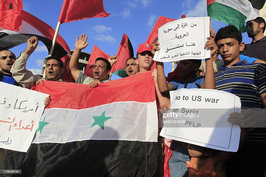 Palestinians from the Popular Front for the Liberation of Palestine (PFLP) wave the Syrian flag and shout slogans as they protest in Rafah, in the southern Gaza Strip, on September 3, 2014, against US and French military intervention in Syria. More than two million Syrians have fled their country, the UN refugee agency said Tuesday, as US officials sought congressional support for military strikes on the Damascus regime. Placard to right reads in Arabic 'From Gaza to Syria.... Damascus is here.'