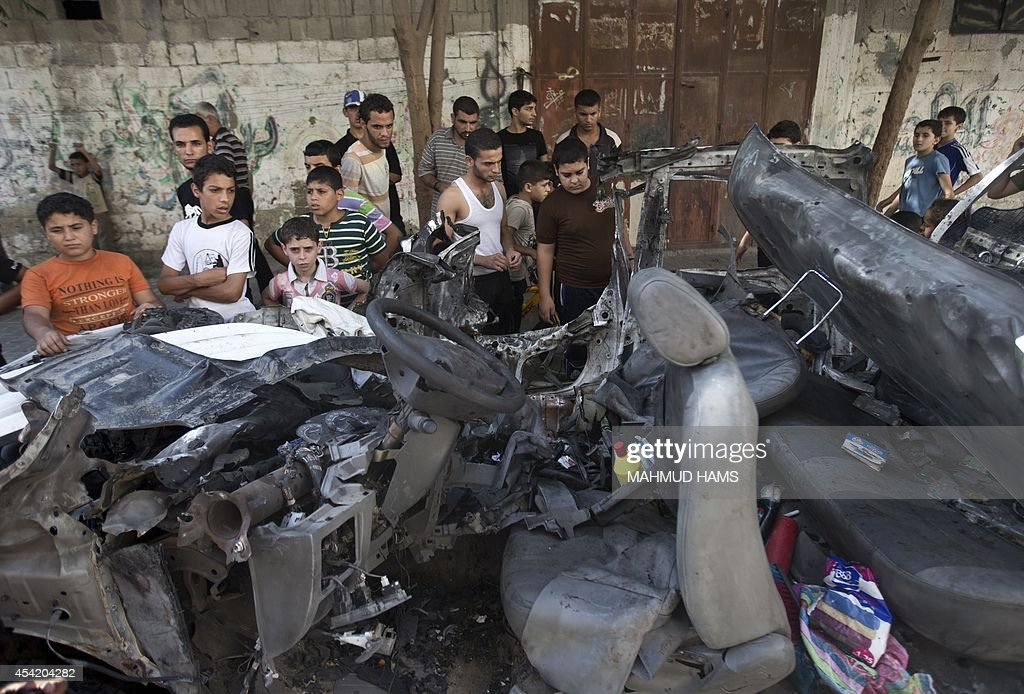 Palestinians gather around a burnt car of the company of electricity that was hit by an Israeli air strike in Beit Lahia City on August 26, 2014 in Beit Lahia in the northern Gaza Strip. The Palestinians said they had reached agreement with Israel on a 'permanent' halt to seven weeks of bloodshed in and around Gaza although Israel was silent on the claimed deal.