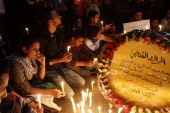 Palestinians gather around a wreath mourning the death of Italian activist Vittorio Arrigoni who was killed by a Salafist group of radical Islamists...