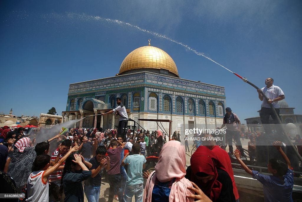 Palestinians gather around members of the Palestinian Red Crescent as they spray people with water to cool off in front of the Dome of the Rock in Jerusalem's Al-Aqsa mosque compound during the last Friday prayers of the holy Muslim fasting month of Ramadan, on July 1, 2016. / AFP / AHMAD