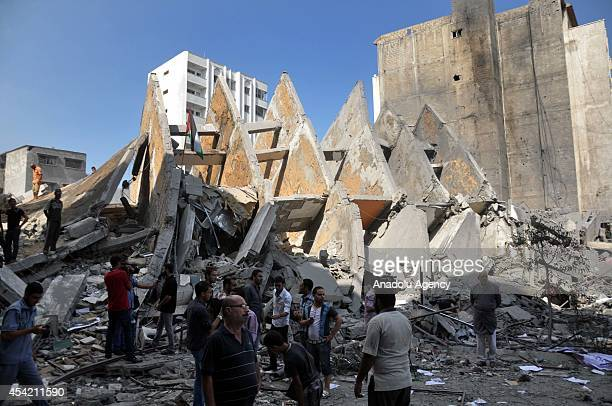 Palestinians gather around the remains of Basha Tower containing apartments and offices hit by Israeli forces in Gaza city Gaza on 26 August 2014