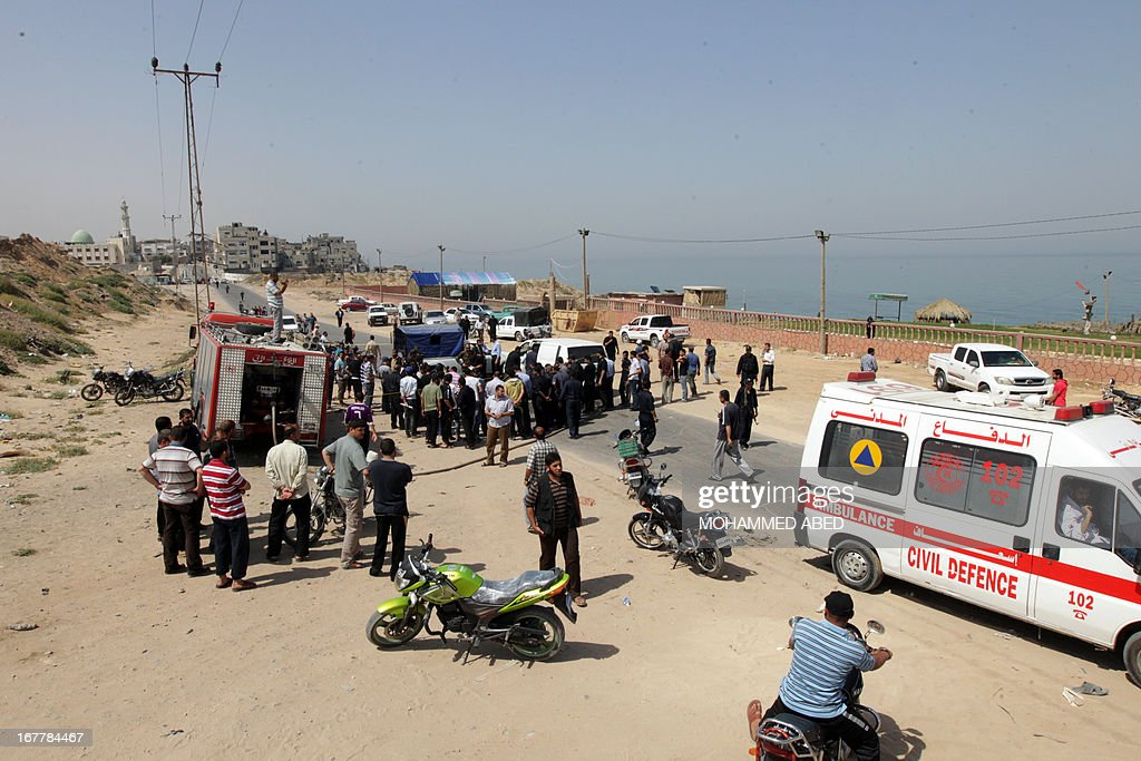 Palestinians gather around the scene following an Israeli raid on Gaza City, on April 30, 2013. An Israeli air strike on Gaza City killed one person and wounded another, Gaza's Hamas-run health ministry said.