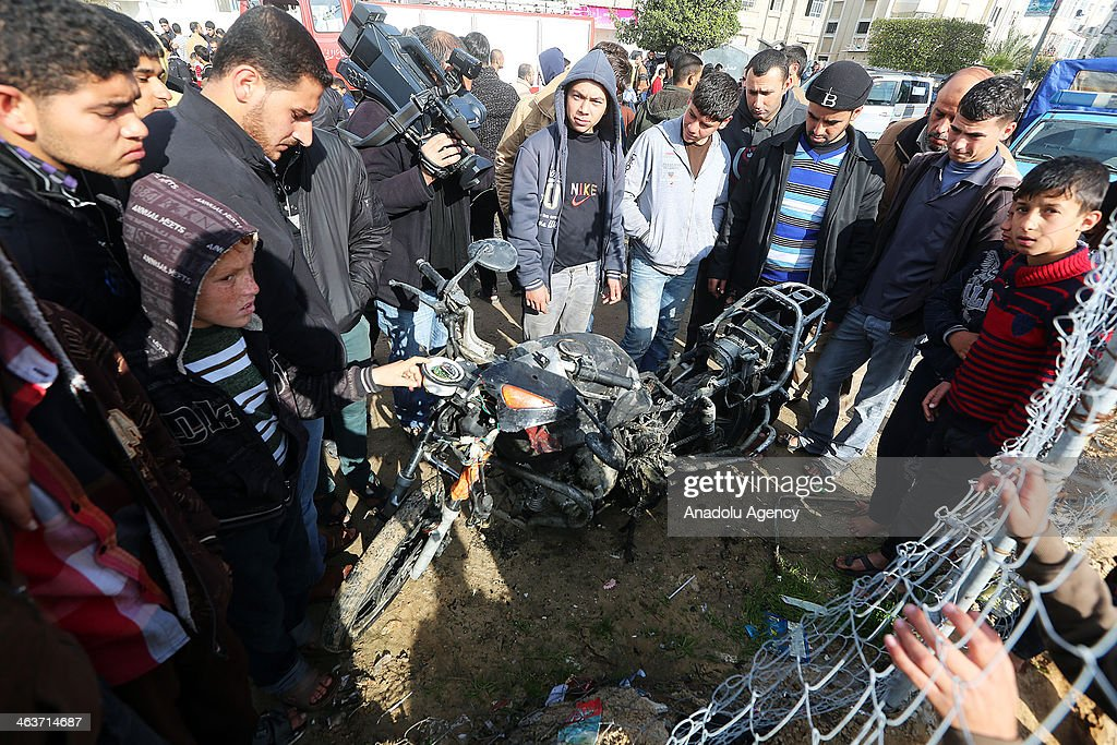Palestinians gather around the wreckage of a motorcycle targeted by an Israeli airstrike on January 19, 2014 in Gaza City. Israeli aircraft attacked two sites of Ezzedeen Al-Qassam Brigades, the armed wing of the Palestinian resistance group Hamas, in the Gaza Strip. Two Palestinians, including a child, were injured Sunday in an Israeli raid on the north of Gaza City, eyewitnesses said.
