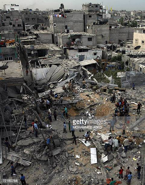 Palestinians gather over the debris of destroyed houses targeted by an Israeli missile attack in the Jabalia refugee camp north of Gaza City 12...