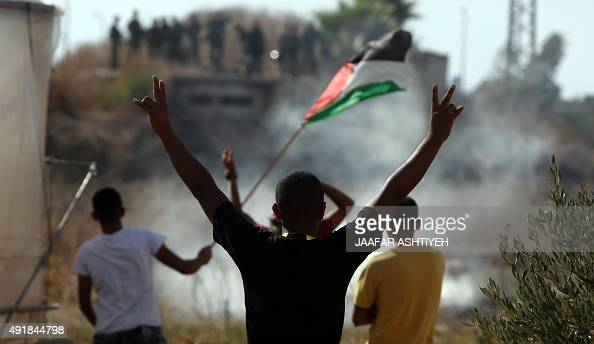 Palestinians gesture towards Israeli soldiers in the West Bank Palestinian town of Tulkarem on October 8 2015 following days of unrest including...