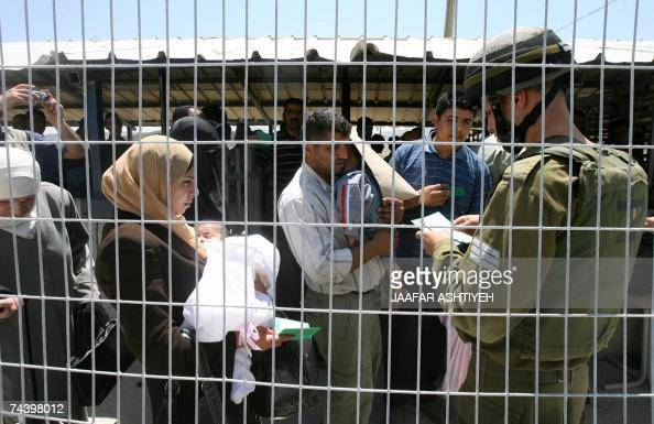 Palestinians have their IDs checked at the Hawara Israeli manned checkpoint as others rally close by to mark the 40th anniversary of the outbreak of...