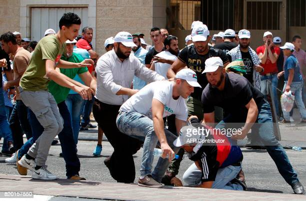Palestinians help a man hit by a rubber bullet rise from the ground during clashes with Israeli forces after Friday prayers at the main entrance of...