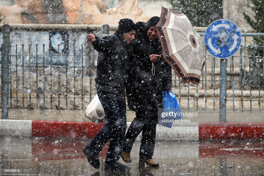 Palestinians hide behind an umbrella as they walk through the first falling snow of the year in the West Bank city of Ramallah on January 9, 2013. Meteorological services expected no improvement in the weather until January 10, as temperatures have dropped below the seasonal norm in many countries of the region, and the snow fell in Syria, Lebanon, the Palestinian Territories, Israel and Jordan. AFP PHOTO/ABBAS MOMANI