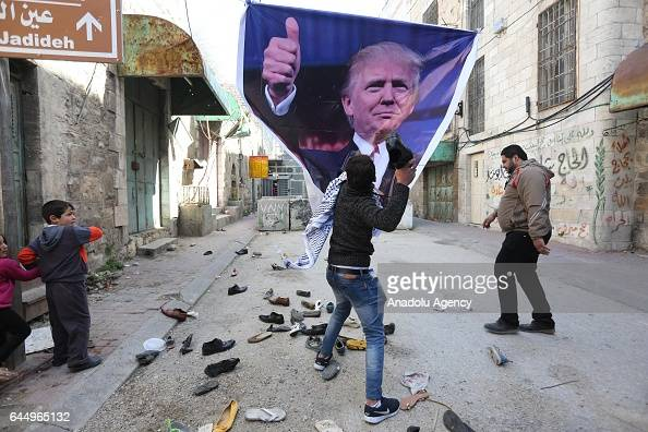 Palestinians hit a US President Donald Trump poster to condemn Trump's policies as they stage a protest against Israeli Government's violations over...