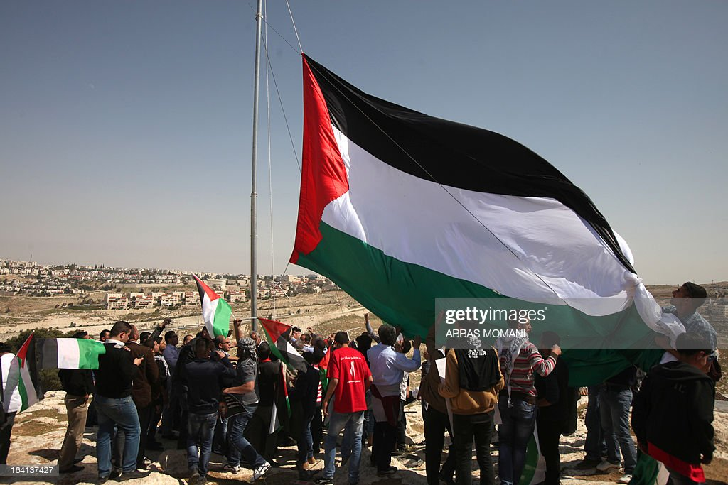 Palestinians hoist a huge Palestinian flag close to Israel's largest Jewish settlement of Maale Adumin on the outskirts of Jerusalem where the US President Barak Obama is visiting on March 20, 2013, on the first day of his three day visit.