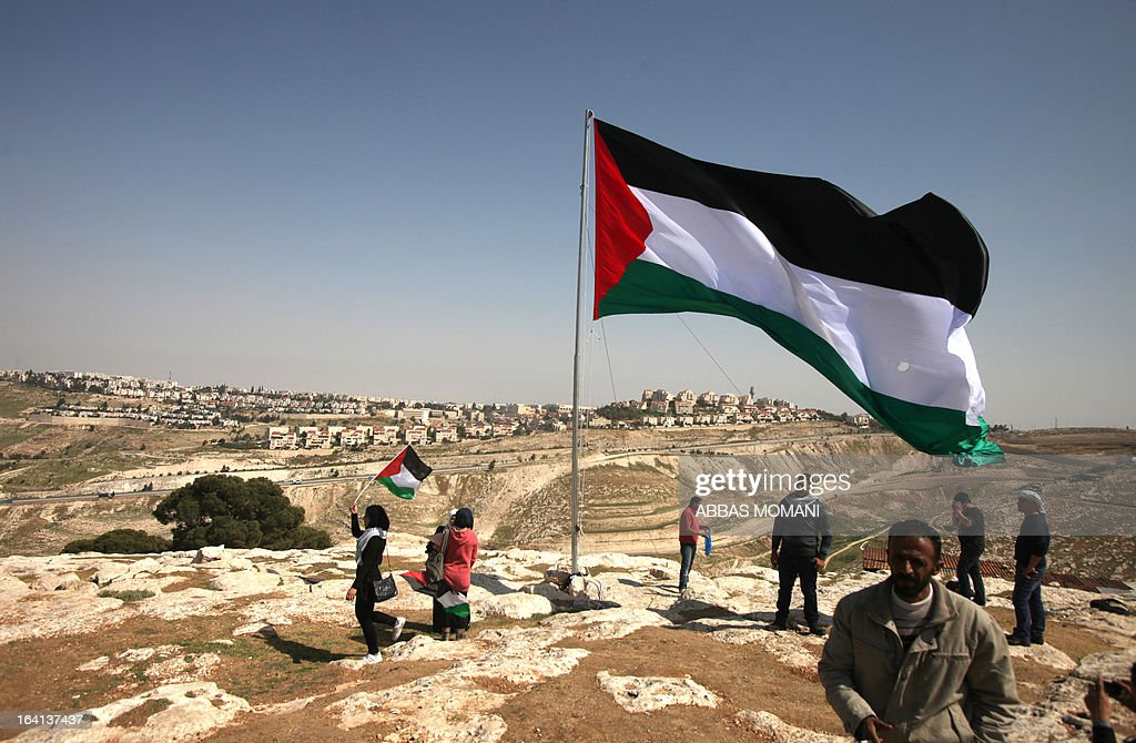 Palestinians hoist a huge Palestinian flag close to Israel's largest Jewish settlement of Maale Adumin on the outskirts of Jerusalem where the US President Barak Obama is visiting on March 20, 2013, on the first day of his three day visit. AFP PHOTO/ ABBAS MOMANI
