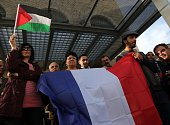 Palestinians hold a French and Palestinian flag as they call for France to vote for the recognition of a Palestinian State outside a French and...