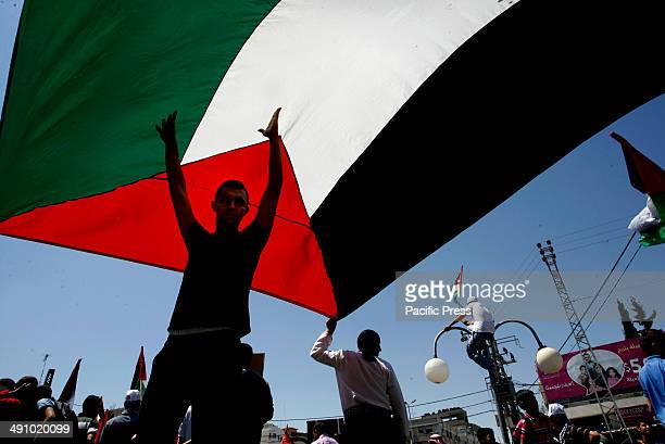 Palestinians hold a large Palestinian flag during a rally ahead of the 66th anniversary of Nakba in Rafah in the southern Gaza Strip Palestinians...
