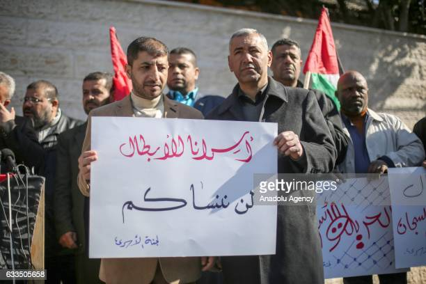Palestinians hold banners during a protest against Israeli violations directed at prisoners held in Israeli jails in front of the International Red...