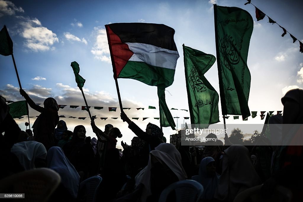 Palestinians hold flags as Hamas Political Bureau Vice President Ismail Haniyeh gives a speech during a festival in Gaza City, Gaza on April 28, 2016.