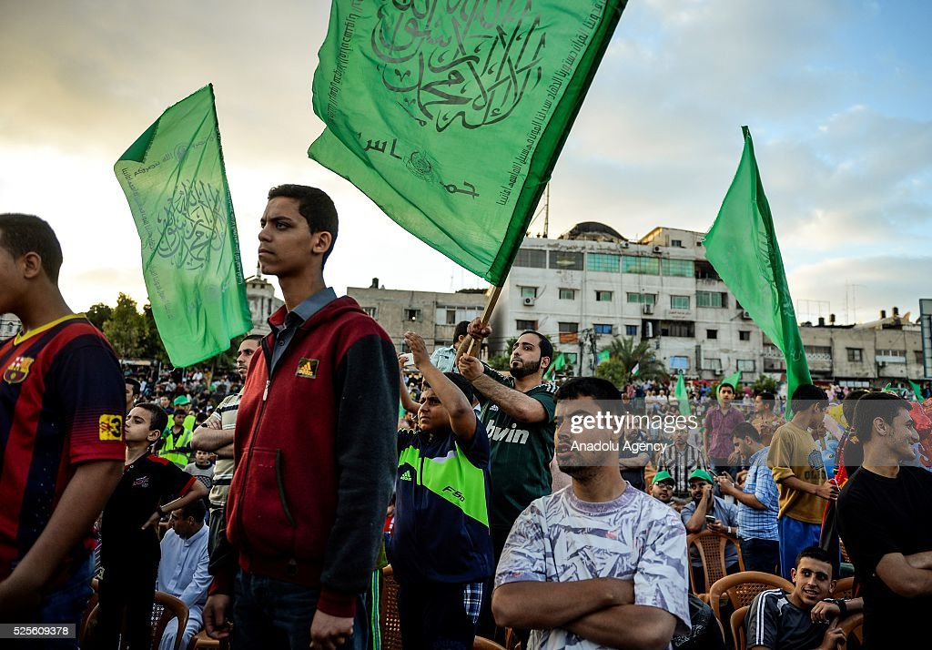 Palestinians hold flags as Hamas Political Bureau Vice President Ismail Haniyeh speaks during a festival in Gaza City, Gaza on April 28, 2016.