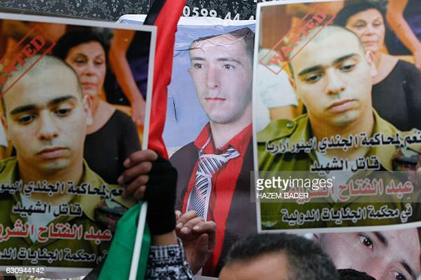 Palestinians hold posters as they gather in the street in the West Bank town of Hebron on January 4 during the trial of Israeli soldier Elor Azaria...