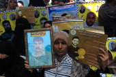 Palestinians hold posters of jailed Palestinian football player Mahmud Sarsak and prisoner Akram Rikhawi during a rally in solidarity with two...