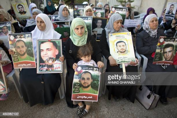Palestinians hold posters with slogans and portraits of detainees during a demonstration on June 10 2014 outside the Red Cross building in Jerusalem...