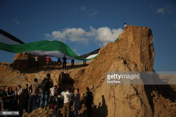 Palestinians hold their country's national flag as they attend a rally against the demolition of the Tel EsSakan hill south of Gaza City on October...