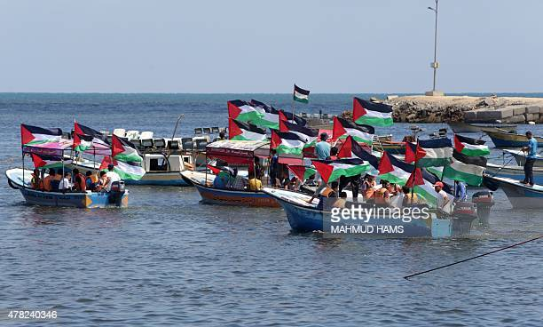 Palestinians hold their national flag as they ride boats during a rally to show support for activists aboard a flotilla of boats who are soon to set...