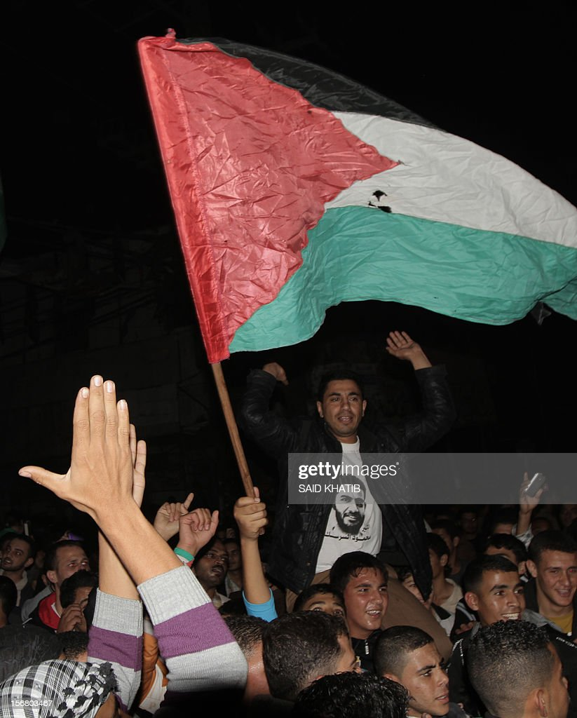 Palestinians hold up their national flag as they celebrate the beginning of the truce with Israel in Rafah town in the southern Gaza Strip on November 21, 2012. Palestinians in Gaza took to the streets to celebrate the start of a truce deal with Israel that was announced in Egypt on the eighth day of violence in and around Gaza.