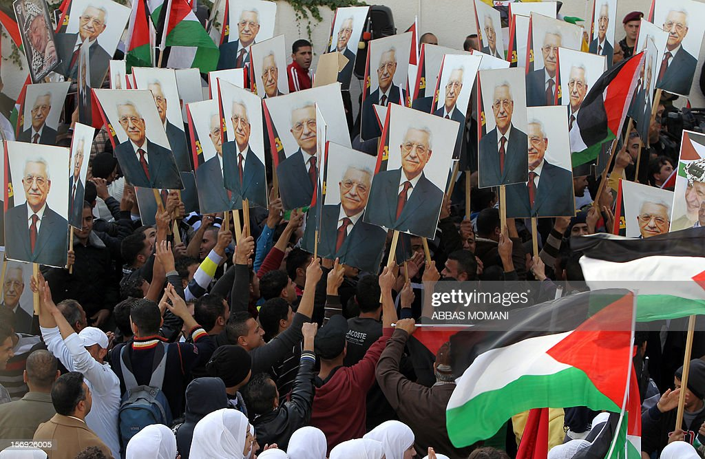 Palestinians hold-up posters of their President Mahmud Abbas as they wait for him to give a speech at his headquarters in the West Bank city of Ramallah, on November 25, 2012, where he said he was 'fully confident' ahead of a fresh attempt to seek upgraded Palestinian status at the United Nations on November 29. AFP PHOTO / ABBAS MOMANI
