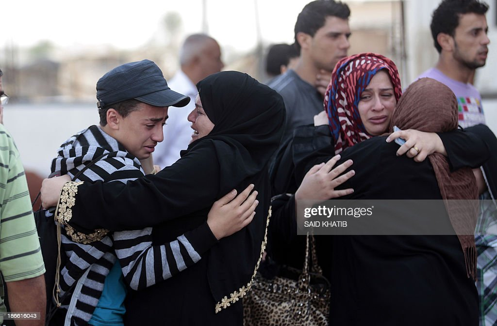 Palestinians hug each other before leaving to cross into Egypt at the Rafah crossing terminal in the southern Gaza Strip on November 02, 2013. Hundreds of patients, students and foreign residents from the Palestinian side have rushed to the Rafah crossing after the Egyptian announcement of re-opening it for 6 days.