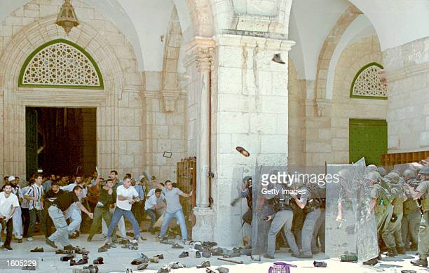 Palestinians hurl shoes at Israeli police at the entrance to alAqsa Mosque July 29 2001 during clashes on the Temple Mount in Jerusalem''s Old City